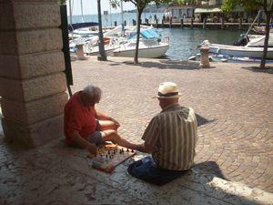Dos vecinos juegan al ajedrez en el puerto de Gargnano