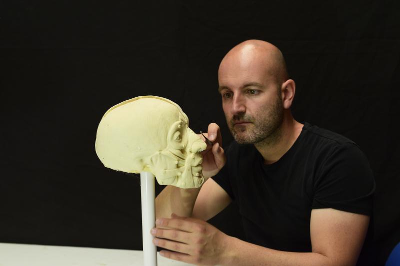 Juan Villa realizando el proceso de modelaje de un busto